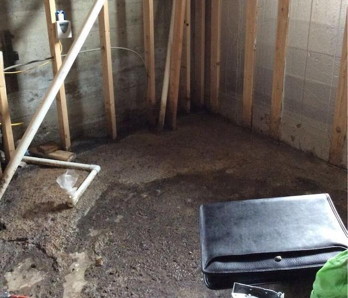 Basement with muddy debris on the floor