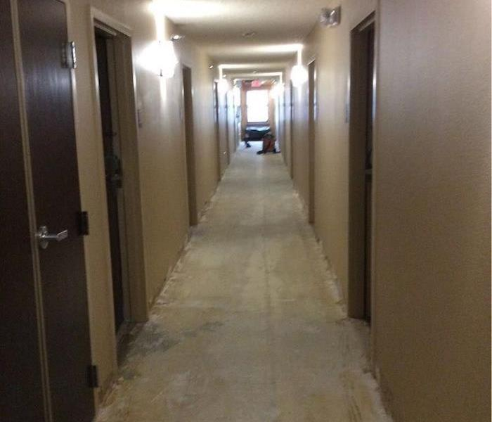 A long hallway with water removal equipment in the background