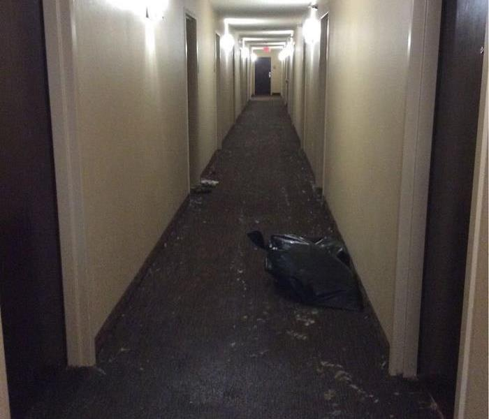 Office hallway with a trash bag and debris on the floor